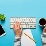 One hand on desktop keyboard and the other holding a coffee mug over a blue desk