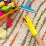 Hand with gloves on cleaning a carpet with toys