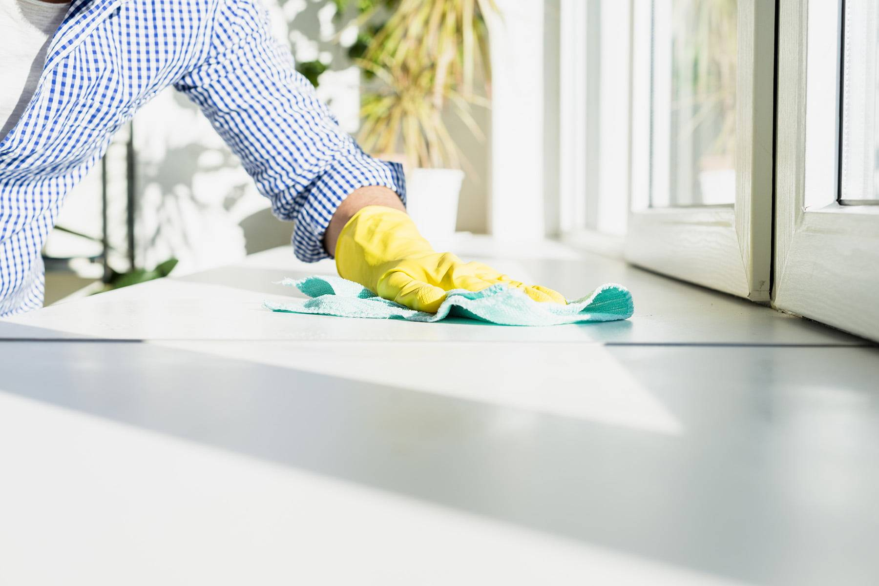 Man with a checkered shirt on cleaning a kitchen bench