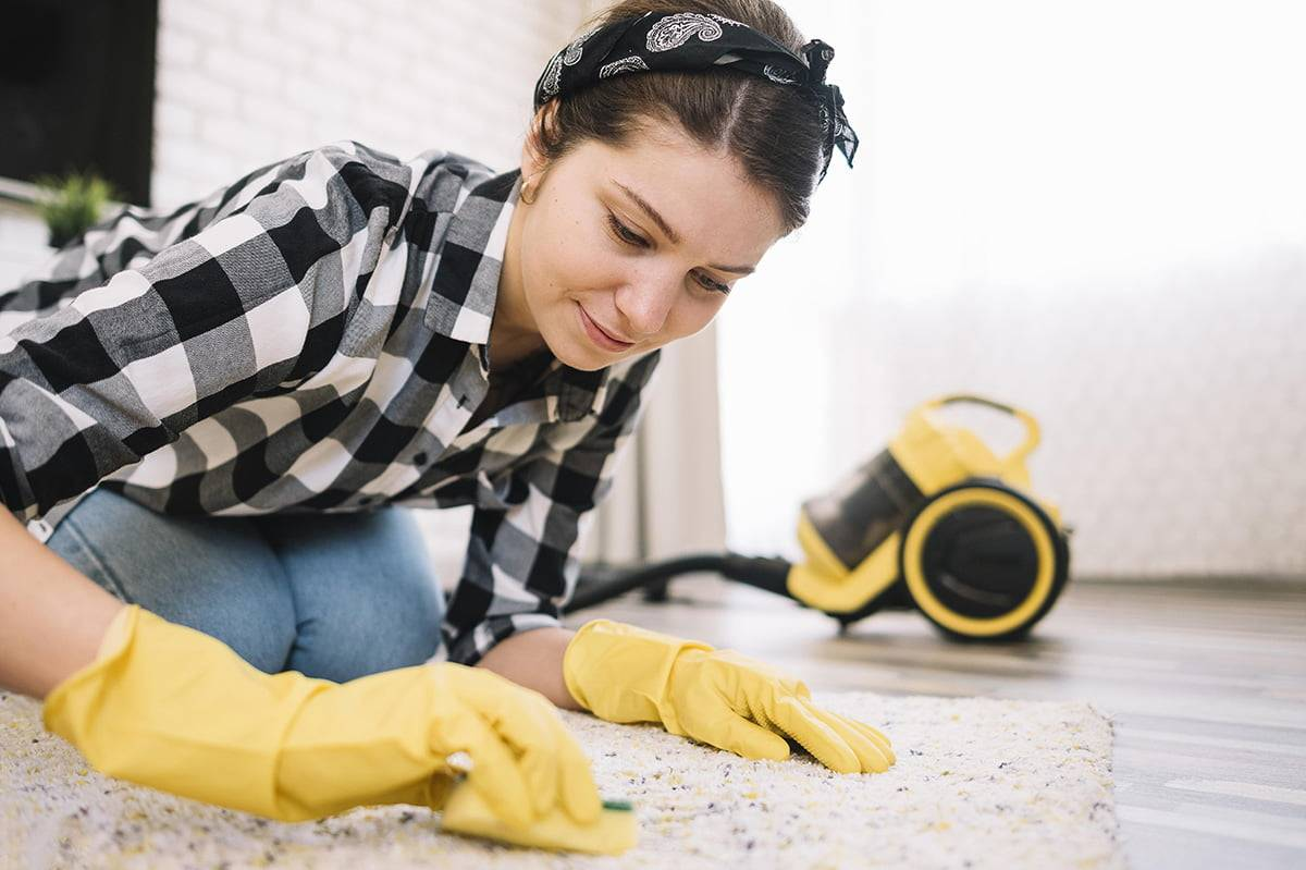 Young woman with checkered shirt cleaning a carpet rug